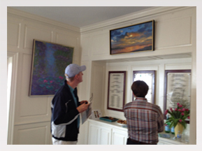 Two guests admiring Daybreak, which is a painting of a sunrise over Coronado, California.